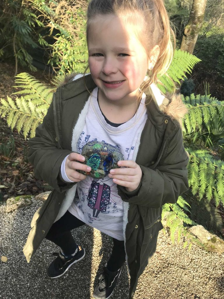Girl poses with painted pebble she found at Trelissick Gardens. Part of the Kernow Rocks! initiative. Go seeking for hidden painted rocks