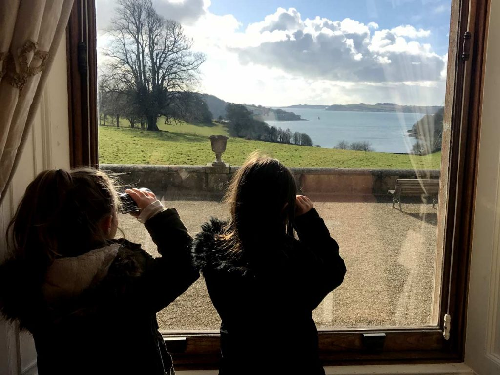 Two girls admire the view over the River Fal from a window Trelissick house